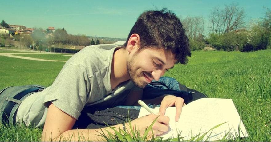 איש צעיר כותב על הדשא