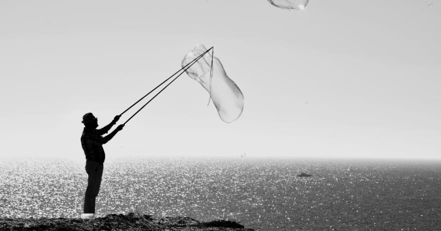 איש מפריח בועות סבון ענקיות על חוף הים (CC0)