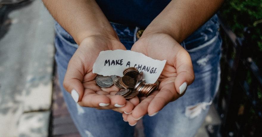 אשה מחזיקה מטבעות בידיים פתוחות, עם פתק ועליו הכיתוב עשו שינוי (צילום: rawpixel / CC0)